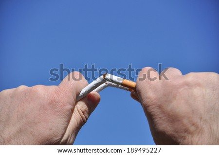 Spring is a good time to stop Smoking. Broken cigarette in his hand, against the background of the spring sky.
