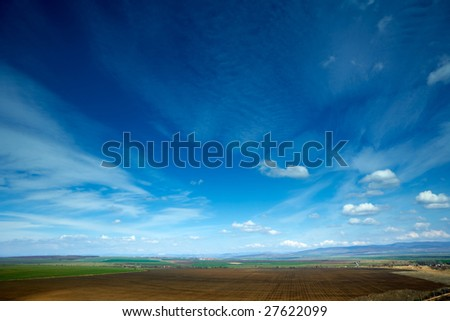 Spring landscape with beautiful colorful blue sky and strange clouds