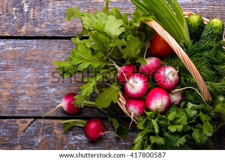 Spring vegetables and herbs in a basket: radishes, onions, parsley, cucumber on a wooden background.