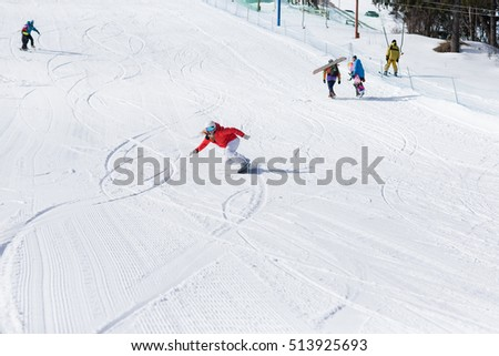 Ssnowboarder on slopes in the sunny morning