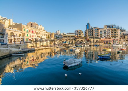 ST JULIANS, MALTA - NOVEMBER 10, 2015: Small fishing boats moored in St Julians and Spinola bay on a sunny day on November 10, 2015 in St Julians, Malta.