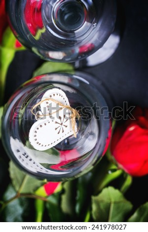 St Valentine greeting card with two champagne glasses with red roses and heart at black stone background. Top view. See series