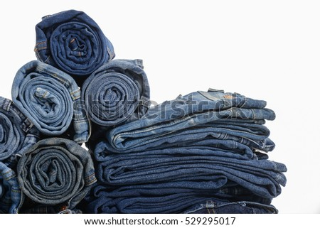 Stack of blue jeans pants isolated on white with natural shadows