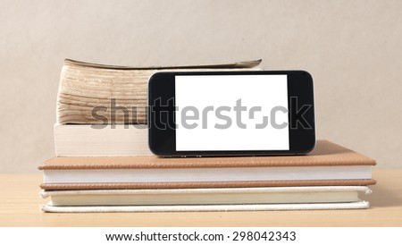 stack of book and smart phone on wood background