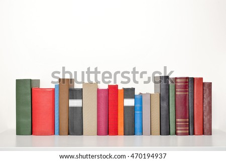 stack of books on the white table near the wall