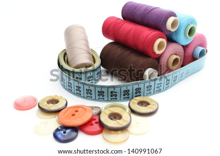 Stack of colorful spools of thread with tape measure and colored buttons