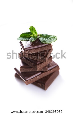 stack of dark chocolate and mint leaf over white background