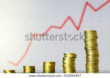 Stack of gold coins against financial graph