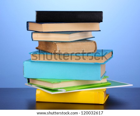 Stack of interesting books and magazines on wooden table on blue background