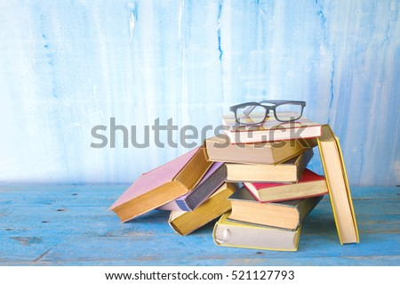 stack of old multicolored books with spectacles, grungy background