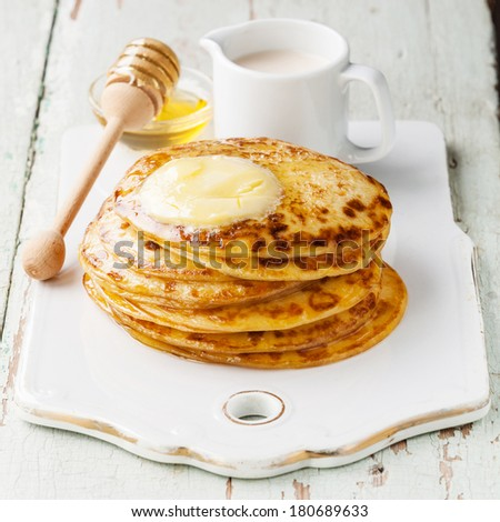 Stack of Small pancakes with butter and honey
