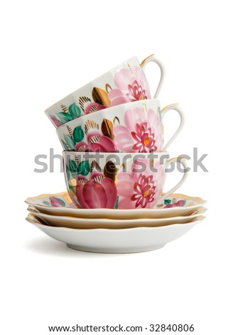 Stack of three porcelain tea cups with saucers isolated