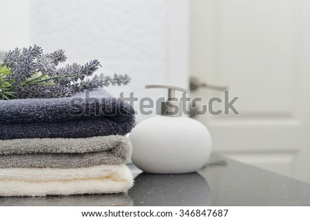 Stack of towels with a soap dispenser  in a bathroom closeup