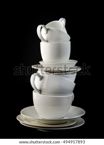 stack of white coffee cups and plates on black background