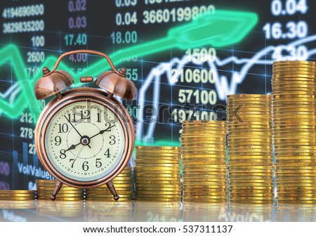 stacks of gold coins step with the vintage clock over the LED display Stock market exchange data background, Business investment and trading concept
