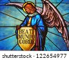Stained glass window of angel holding shield with one of beatitudes in Latin, Blessed are the pure of heart - stock photo