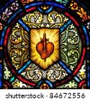 Stained glass window with symbol of heart pierced by a sword - stock photo