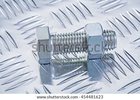 Stainless bolt and threaded nut on grooved metal plate construction concept.
