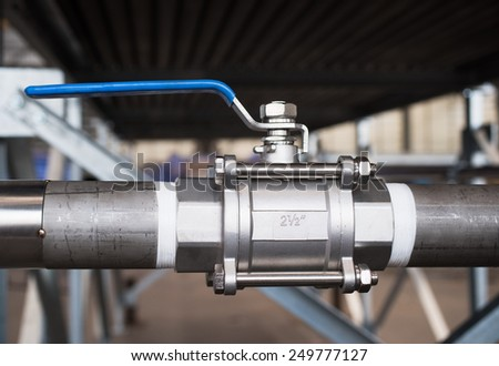 Stainless steel, 2.5 inch ball valve at an industrial workshop. Shallow depth of field with the valve in focus.