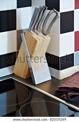 stainless steel knives set on stand in kitchen interior
