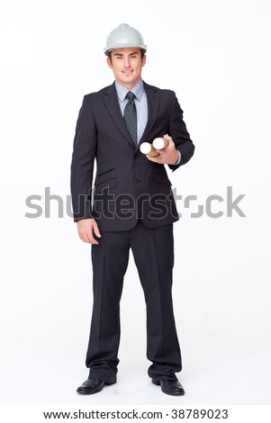 Standing attractive businessman holding blueprints against white