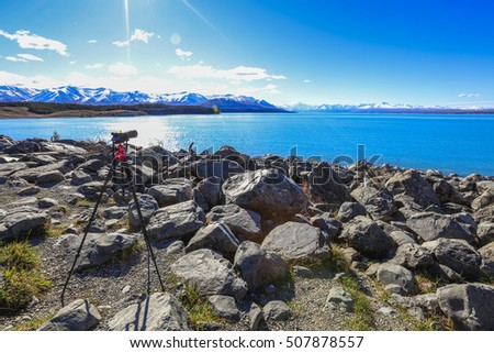Standing camera shooting over sun light at Pukaki Lake view point, New Zealand