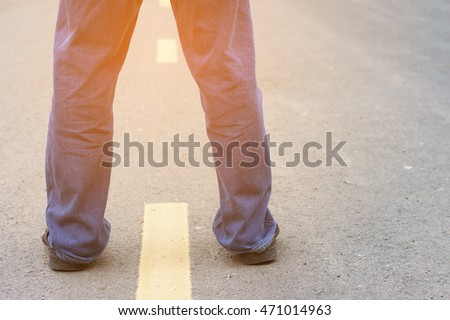 Standing Man Jeans on the asphalt road with path and sunlight, Behind view.