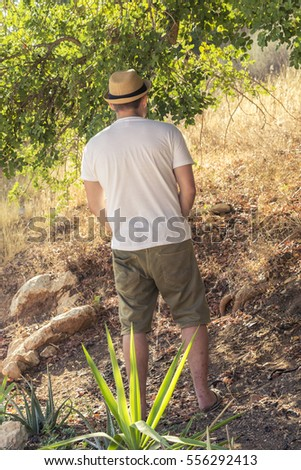 Standing man peeing in autumn forest in nature - incontinence co