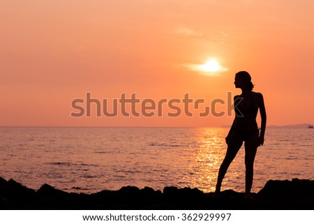Standing woman silhouette on sunset sea background back lit