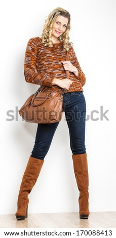 standing woman wearing jeans with a handbag