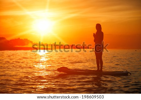 Standup paddle board yoga performed by beautiful girl on the bright sunset background, yoga training on the beach