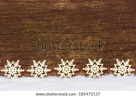 Stars in the snow in front of wood