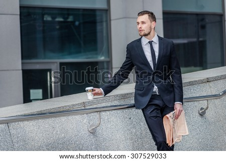 Start the day. Confident businessman coming down the stairs to the street and drink coffee at the same time holds a morning business newspaper