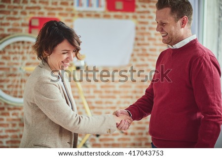 Start up office. Handshake. Female and male smiling.