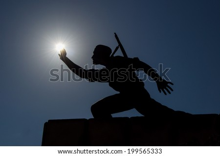 statue of a soldier grabbing backlit sun with hand