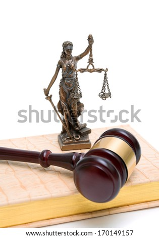 statue of justice, gavel and book on a white background. vertical photo.