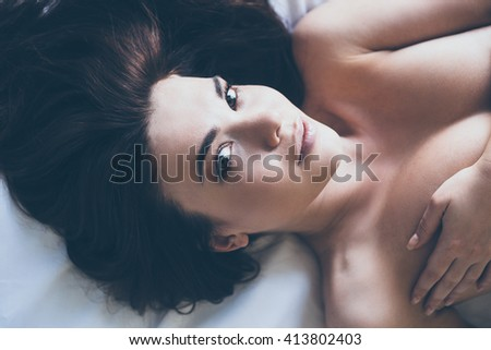 Staying in bed all day long. Close-up of beautiful young topless woman looking at camera while lying in bed