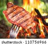 Steak on a fork. In the background a bonfire in the forest. - stock photo