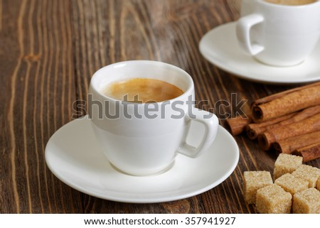 Steaming espresso in a white cup, cinnamon and brown sugar on wooden table. Selective focus.