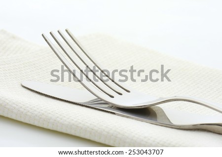 Steel fork and knife in a linen serviette on white background