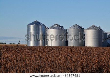 Steel silos in a grassy field in rural