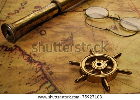 Steering wheel, glasses and spyglass on the old map