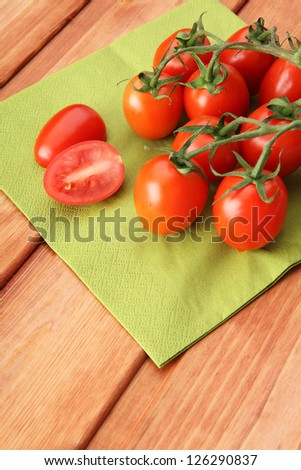 Stem of cherry tomatoes on green napkin