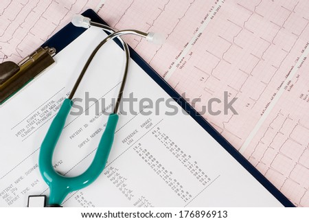 Stethoscope and blood test results on electrocardiogram (ECG) chart