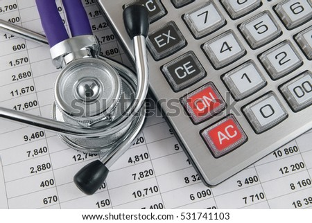 Stethoscope and calculator on financial document