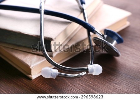 Stethoscope on books on wooden table, closeup