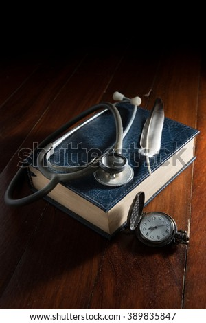 Stethoscope with feather on book and watch.