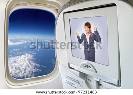 Stewardess on the plane on monitor. Information from Air hostess in display plane flying over the world. Screen television in plane next to window overlooking the globe. Aircraft flies over the Earth.