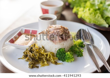 Stewed pork leg on rice on wooden table, asian food.