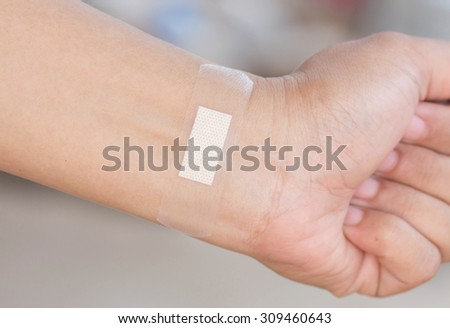 Sticking plaster on the wrist.